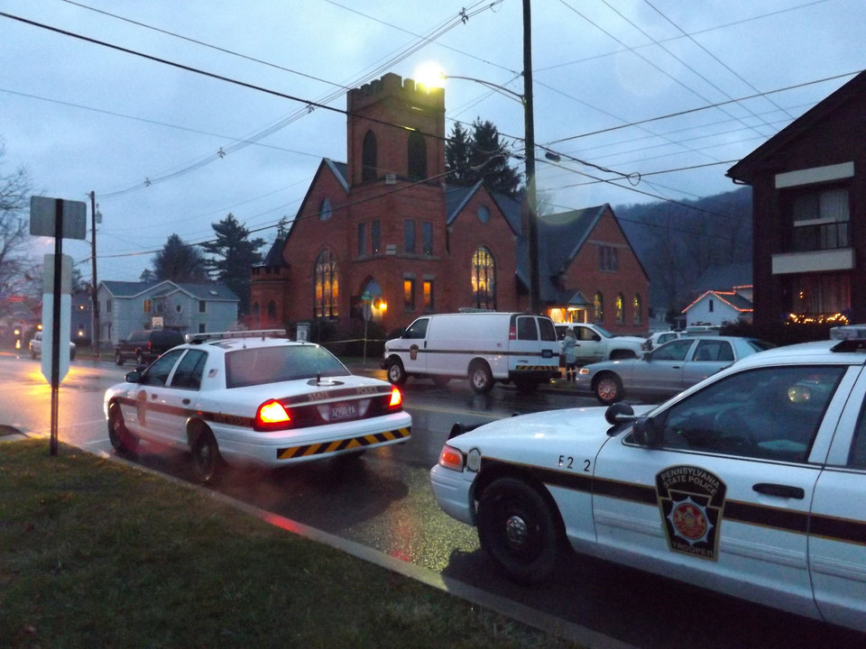 Photo - Police cars are parked at the 180-year-old First United  Presbyterian Church of Coudersport Sunday morning, Dec. 2, 2012, where church organist Darlene Sitler, 53, was shot  to death by her ex-husband Gregory Eldred, 52, during a worship service.  Eldred, an elementary school music teacher, walked into the church in the middle of Sunday services and shot and killed his ex-wife as she sat in a pew, police said. (AP Photo/The Bradford Era, Amanda Jones)