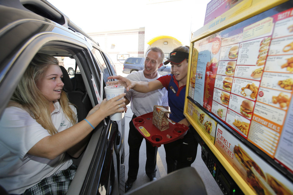 Sonic customer Madison Wall, left, is surprised with a free meal by State Farm Insurance agent Michael Garey and Sonic carhop Kellye Tallent at the Sonic drive-in at 5625 N Western Ave. in Oklahoma City.  Photos by Steve Gooch, The Oklahoman
