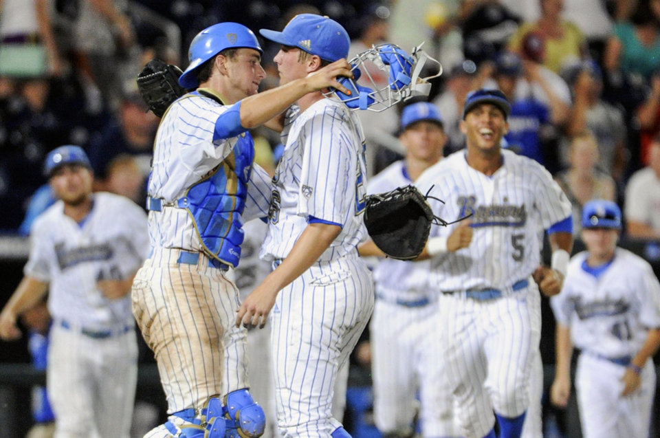 Photo - UCLA closing pitcher David Berg, right, and catcher Shane Zeile hug after an NCAA College World Series baseball game against North Carolina in Omaha, Neb., Friday, June 21, 2013. UCLA won 4-1. (AP Photo/Francis Gardler)