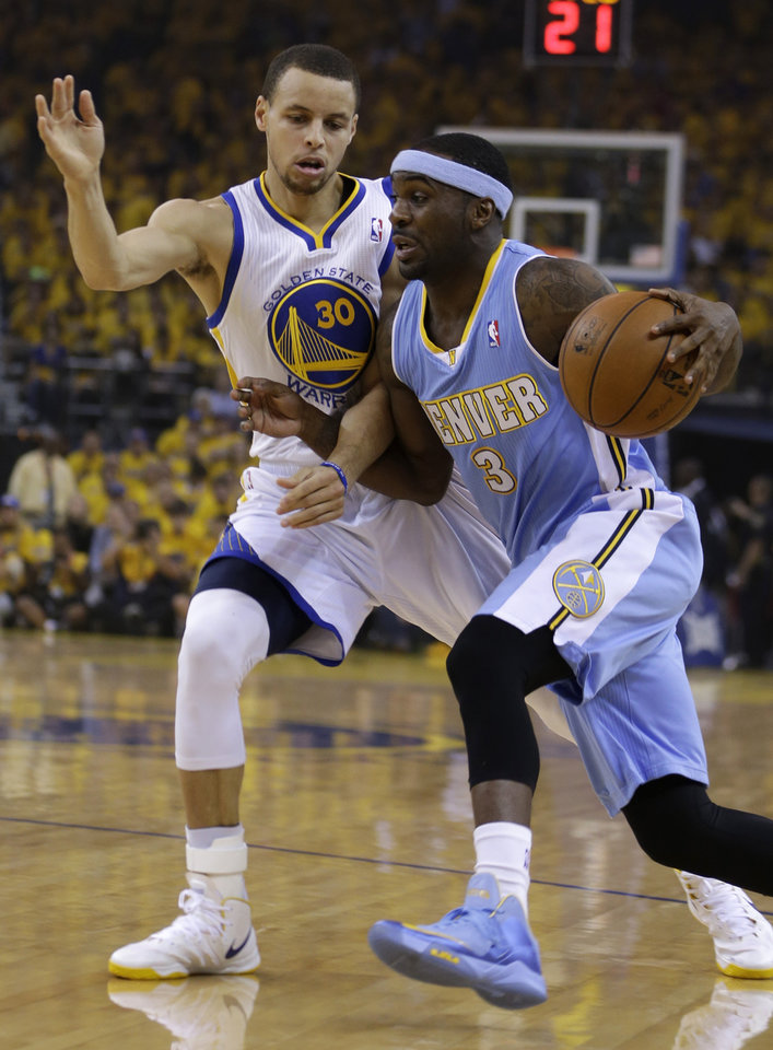 Photo - Denver Nuggets' Ty Lawson, right, drives the ball past Golden State Warriors' Stephen Curry (30) during the first half of Game 4 in a first-round NBA basketball playoff series on Sunday, April 28, 2013, in Oakland, Calif. (AP Photo/Ben Margot)