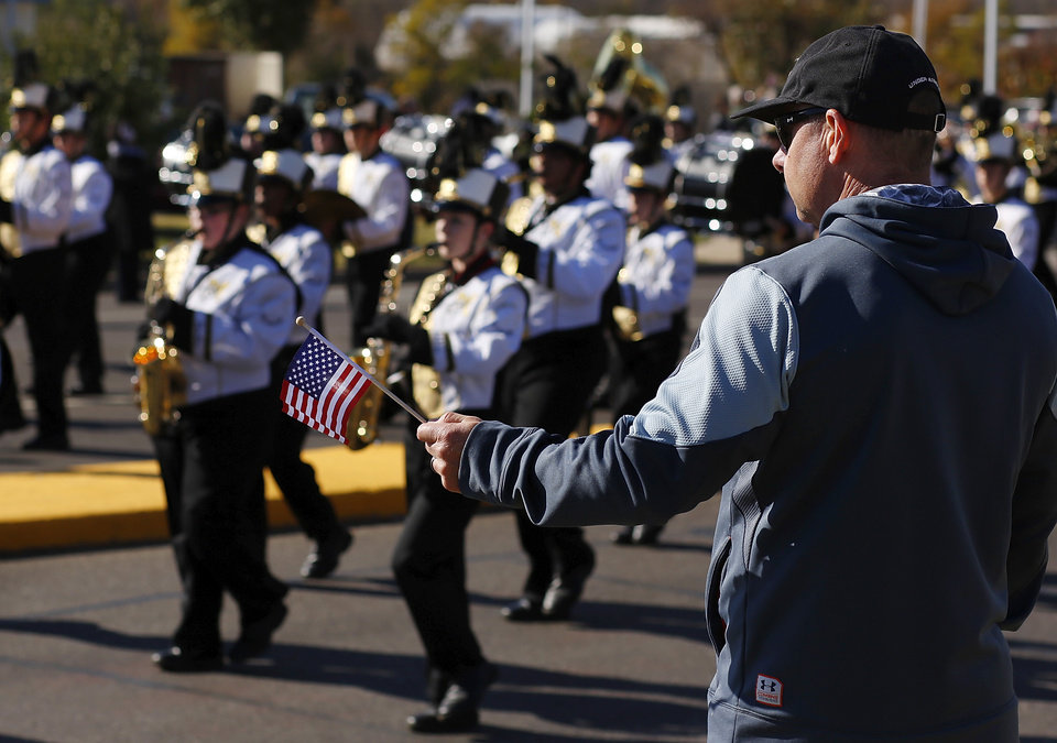 Photo - A man holds out an American flag when the Midwest City High School marching band  plays the US Army song. The city of Midwest City teamed with civic leaders and local merchants to display their appreciation for veterans and active military forces by staging a hour-long Veteran's Day parade that stretched more than a mile and a half along three of the city's busiest streets Monday morning, Nov. 12, 2012. Hundreds of people lined the parade route, many of them waving small American flags that had ben distributed by volunteers who marched near the front of the parade. A fly-over performed by F-16s from the138th Fighter Wing, Oklahoma Air National Guard unit in Tulsa thrilled spectators. Five veterans representing military personnel who served in five wars and military actions served as  Grand Marshals for the parade. Leading the parade was the Naval Reserve seven-story American flag, carried by 100 volunteers from First National Bank of Midwest City, Advantage Bank and the Tinker Federal Credit Union. The flag is 50 feet by 76 feet, weighs 110 pounds and was sponsored by the MWC Chapter of Disabled American Veterans. Photo by Jim Beckel, The Oklahoman