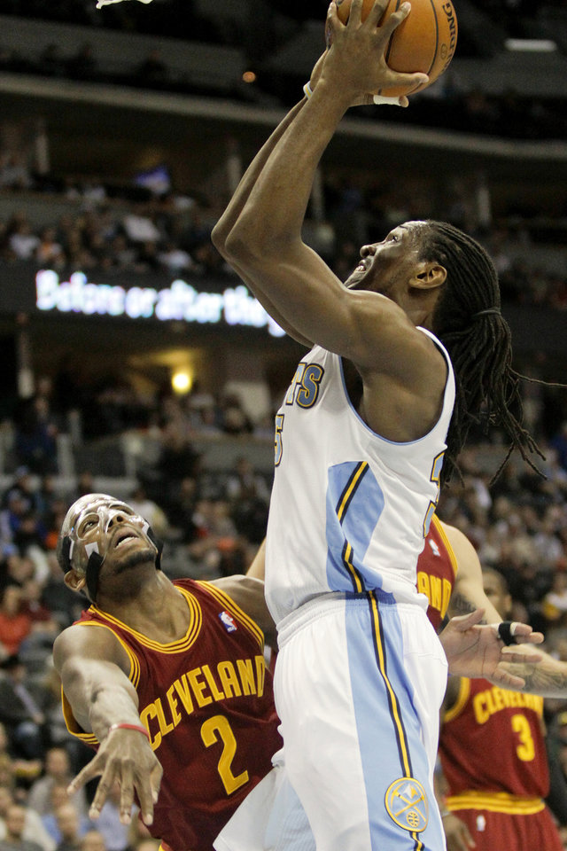 Denver Nuggets' Kenneth Faried, right, shoots over Cleveland Cavaliers' Kyrie Irving, left, during the first quarter of an NBA basketball game Friday, Jan. 11, 2013, in Denver. (AP Photo/Barry Gutierrez)