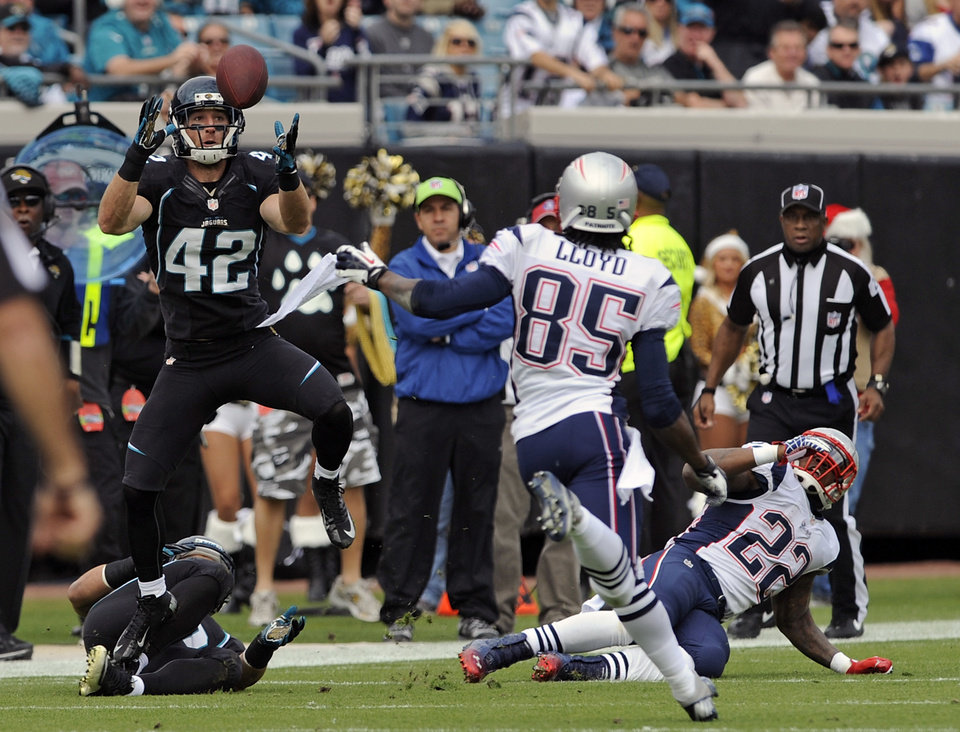 Photo - Jacksonville Jaguars free safety Chris Prosinski (42) intercepts a pass in front of New England Patriots wide receiver Brandon Lloyd (85) and running back Stevan Ridley (22) during the first half of an NFL football game on Sunday, Dec.  23, 2012, in Jacksonville, Fla. (AP Photo/Stephen Morton)