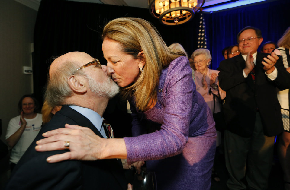 Photo - First Congressional District Democratic candidate Elizabeth Colbert Busch kisses a supporter goodbye after giving her concession speech at the Charleston Renaissance Hotel after losing to Republican Mark SanfordTuesday, May 7, 2013, in Charleston S.C.  In back is her husband Claus Busch. The two were running in a special election for the state's vacant 1st District congressional seat. (AP Photo/Mic Smith)