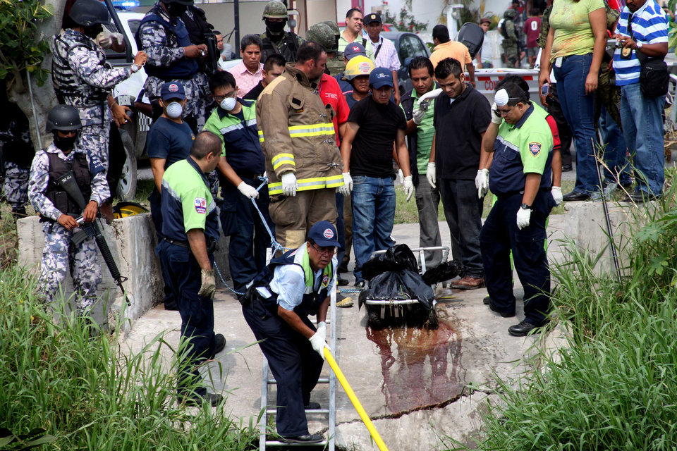 Photo -   Police remove from a canal plastic bags containing the dismembered bodies of four people in Boca del Rio, Mexico, Thursday, May 3, 2012. The bodies were found dumped together in plastic bags by a canal in the eastern Mexican state of Veracruz on Thursday, less than a week after the killing of a reporter for an investigative newsmagazine. At least three of the slain had worked as news photographers. (AP Photo/Felix Marquez)