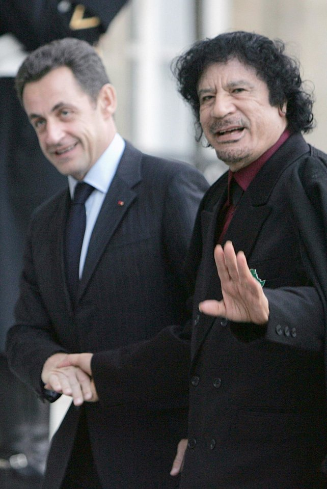 Photo -   FILE- French President Nicolas Sarkozy, left, greets Libyan leader Moammar Gadhafi at his arrival at the Elysee Palace in Paris, in this Dec. 12, 2007 file photo. A former Libyan prime minister Al-Baghdadi Al-Mahmoudi, in a jail near Tunis awaiting possible extradition to Libya, says Moammar Gadhafi's regime financed French President Nicolas Sarkozy's 2007 election campaign, according to his lawyer. Sarkozy vehemently denies the allegations. (AP Photo/Remy de la Mauviniere, File)