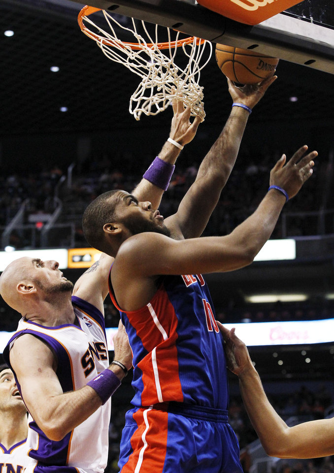 Detroit Pistons' Greg Monroe, right, gets off a shot as Phoenix Suns' Marcin Gortat, left, of Poland, defends in the first half of an NBA basketball game on Friday, Nov. 2, 2012, in Phoenix.(AP Photo/Ross D. Franklin)