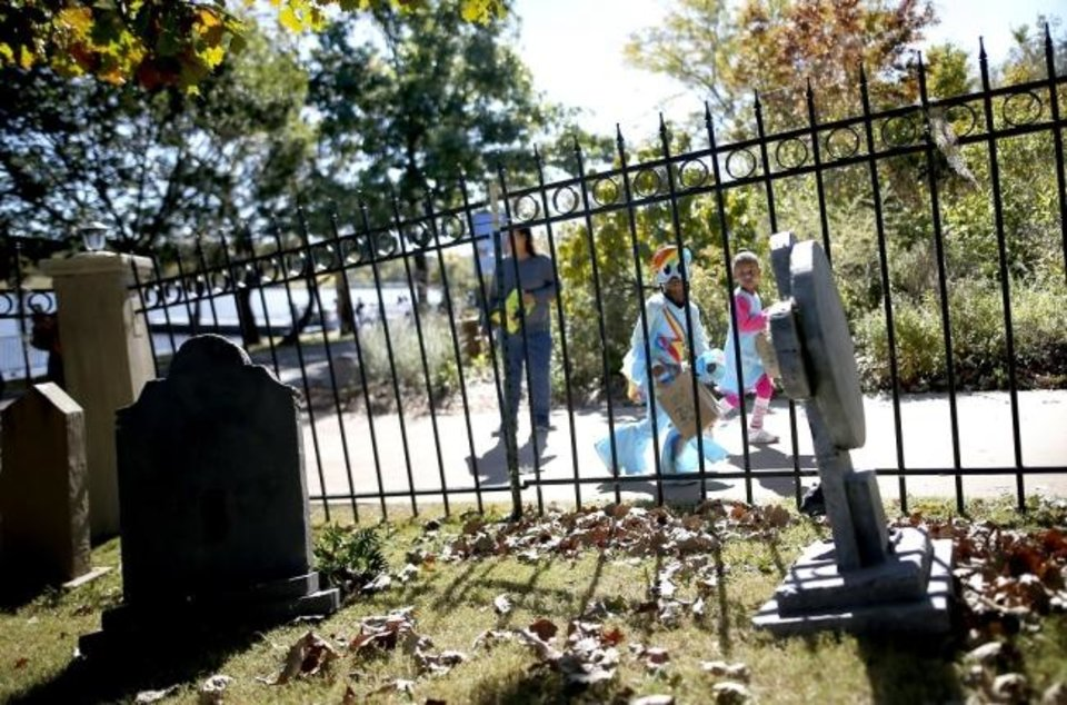 Photo -  Trick-or-treaters look at a graveyard scene during the 2017 Haunt the Zoo at the Oklahoma City Zoo and Botanical Garden. [Sarah Phipps/The Oklahoman Archives]