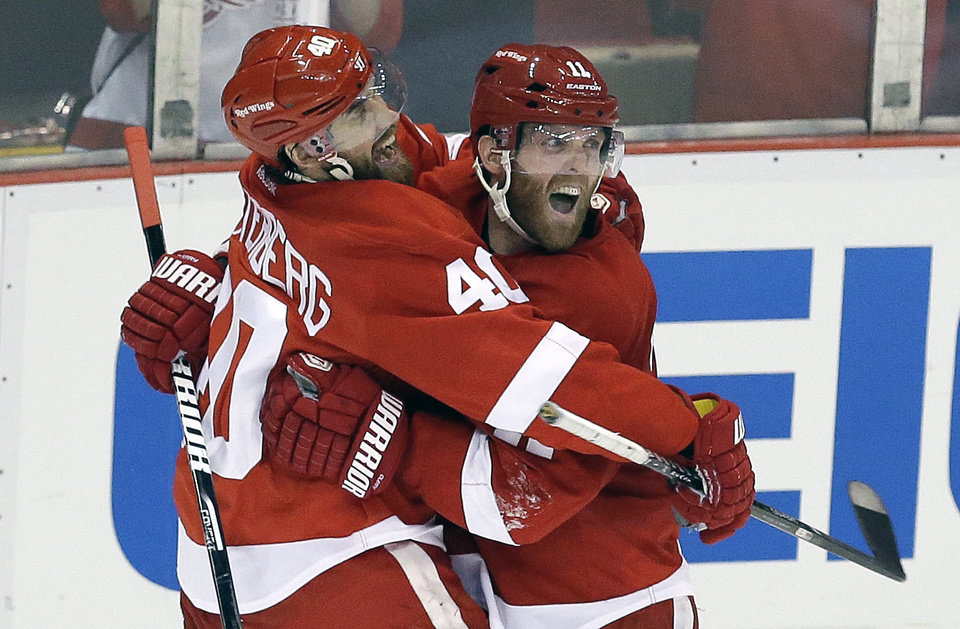 Photo - Detroit Red Wings right wing Daniel Cleary, right, celebrates his empty-net goal against the Chicago Blackhawks with teammate Henrik Zetterberg (40), of Sweden, during the third period in Game 4 of the Western Conference semifinals in the NHL hockey Stanley Cup playoffs in Detroit, Thursday, May 23, 2013. Detroit won 2-0. (AP Photo/Paul Sancya)