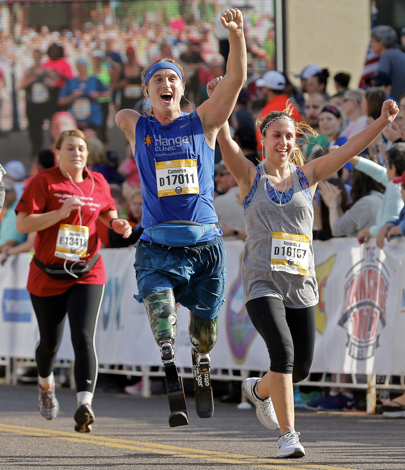 Photo - Cameron Clapp, left, and Amanda Jones celebrate finishing the half marathon during the Oklahoma Memorial Marathon in Oklahoma City, Okla. on Sunday, April 24, 2016.   Photo by Chris Landsberger, The Oklahoman