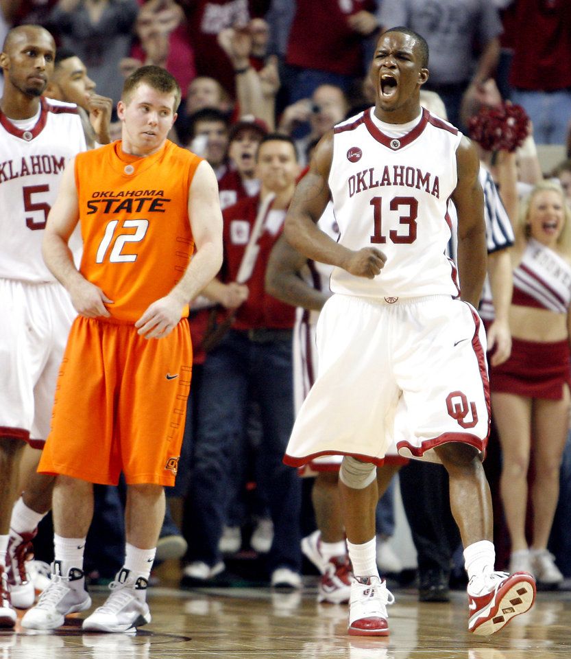Photo - OU's Willie Warren (13) celebrates in front of OSU's Keiton Page (12) in the Sooners 62-57 overtime win in the college bedlam basketball game between The University of Oklahoma Sooners (OU) and Oklahoma State University University Cowboys (OSU) at the Lloyd Noble Center on Monday, Jan. 11, 2010, in Norman, Okla.