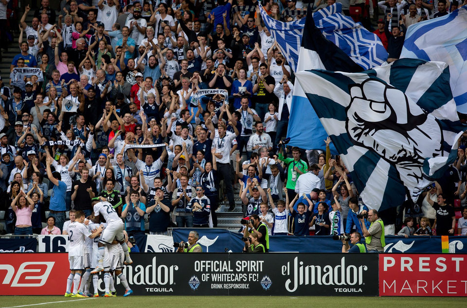 Photo - Vancouver Whitecaps' Erik Hurtado is mobbed by teammates after scoring against the Seattle Sounders during the first half of an MLS soccer game in Vancouver, British Columbia, Saturday, May 24, 2014. (AP Photo/The Canadian Press, Darryl Dyck)