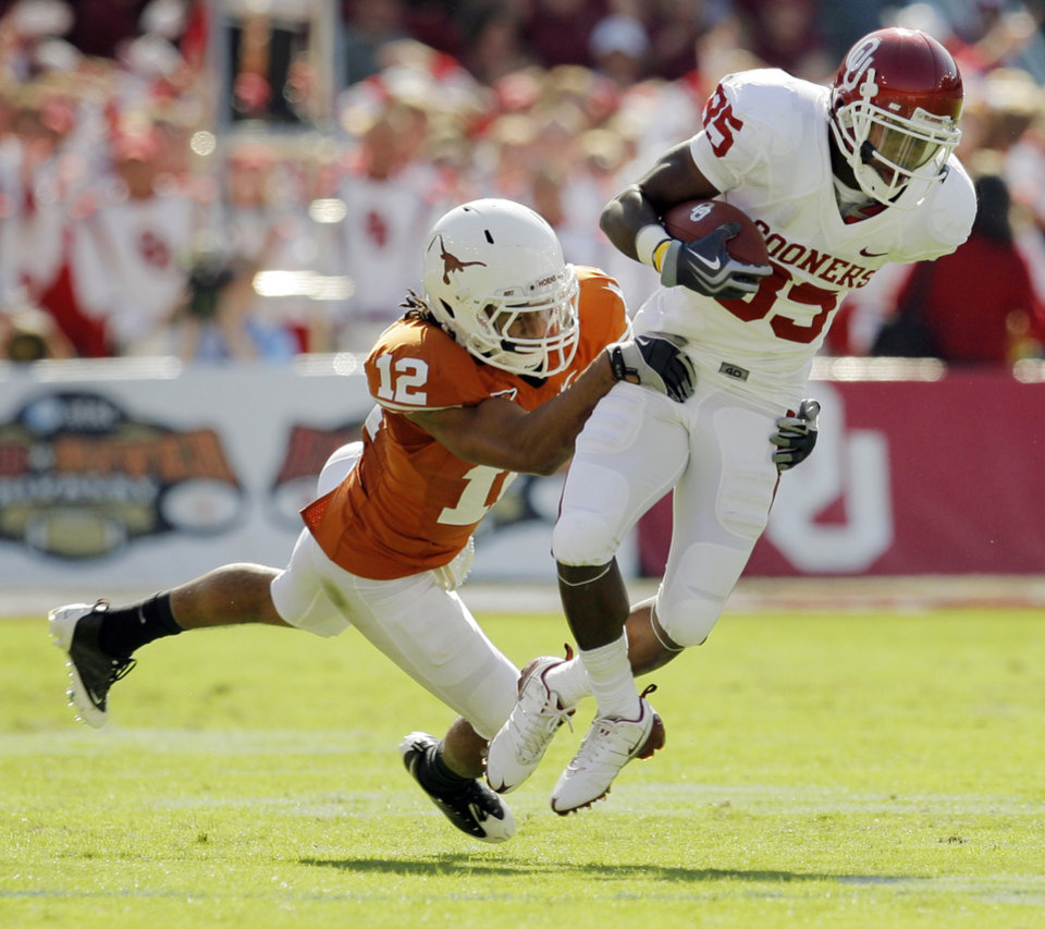 Photo - Earl Thomas (12) of Texas tackles OU's Ryan Broyles (85) after a catch during the Red River Rivalry college football game between the University of Oklahoma Sooners (OU) and the University of Texas Longhorns (UT) at the Cotton Bowl in Dallas, Texas, Saturday, Oct. 17, 2009. Photo by Nate Billings, The Oklahoman