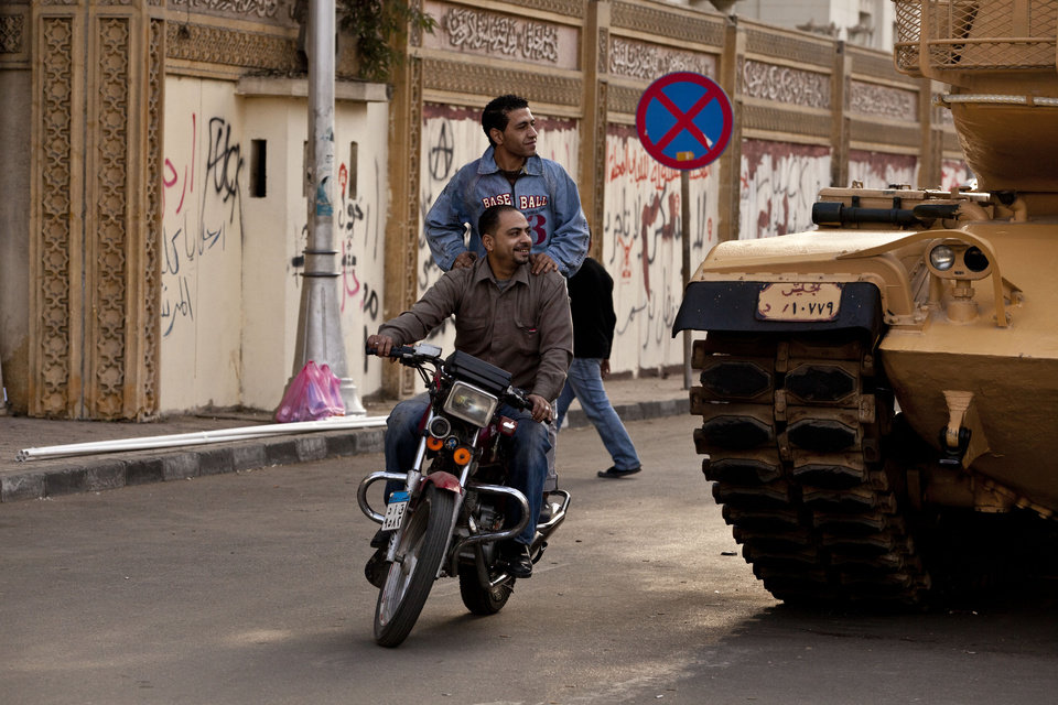 Photo - Egyptians on a motorbike pass a tank staged outside the presidential palace as protesters opposed to Egyptian President Mohammed Morsi gather in Cairo, Egypt, Saturday, Dec. 8, 2012. Egypt's military said Saturday that serious dialogue is the