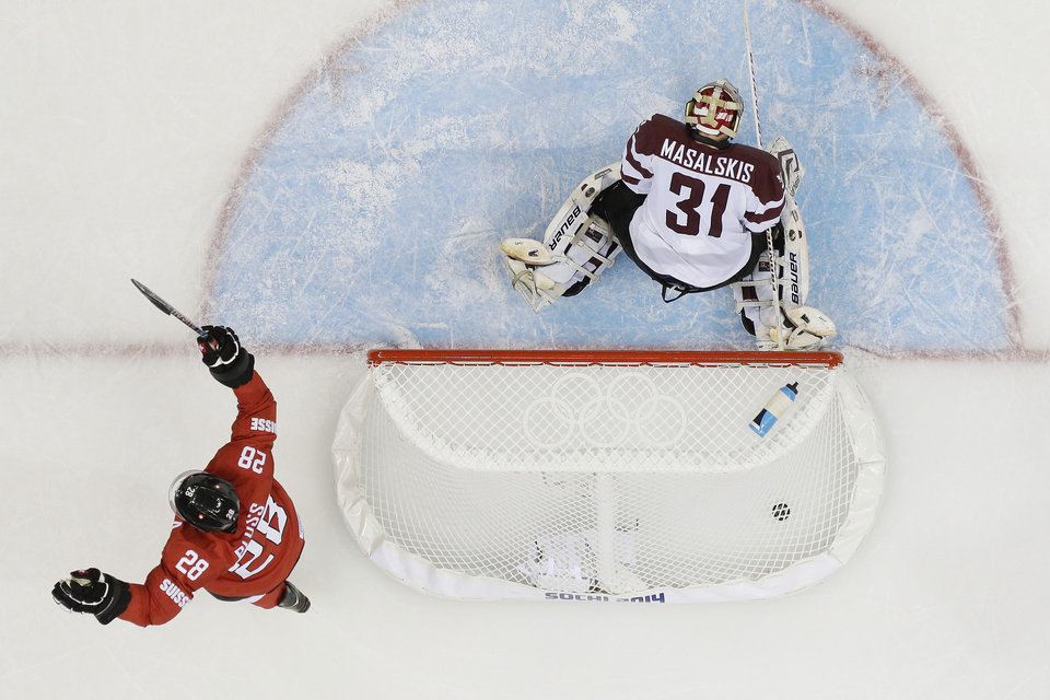 Photo - Latvia goaltender Edgars Masalskis looks down at the ice as Switzerland forward Martin Pluss celebrates the winning goal by Switzerland forward Simon Moser during the closing seconds of the 2014 Winter Olympics men's ice hockey game at Shayba Arena, Wednesday, Feb. 12, 2014, in Sochi, Russia. (AP Photo/Matt Slocum)