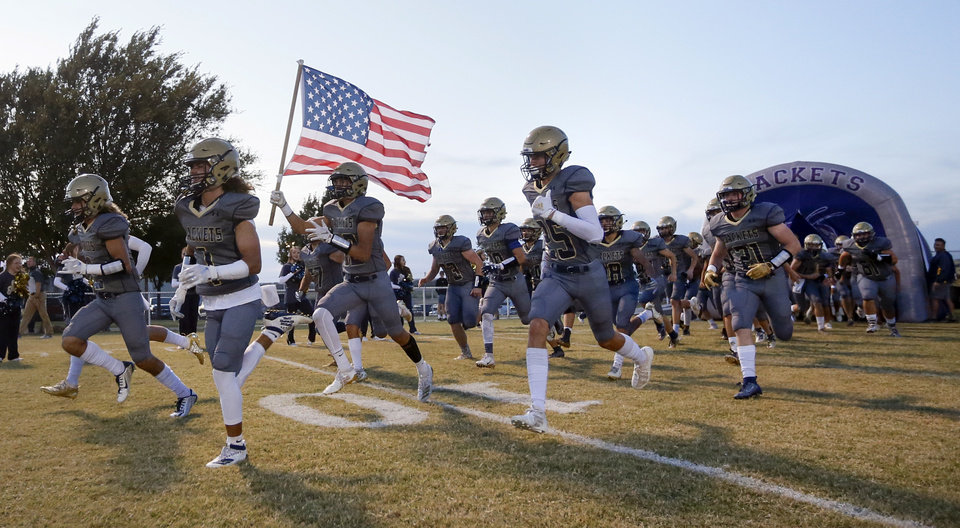 Photo - The Kingfisher Yellowjackets take the field before a high school football game between Perkins-Tryon and Kingfisher in Kingfisher, Okla., Thursday, Oct. 17, 2019. [Nate Billings/The Oklahoman]