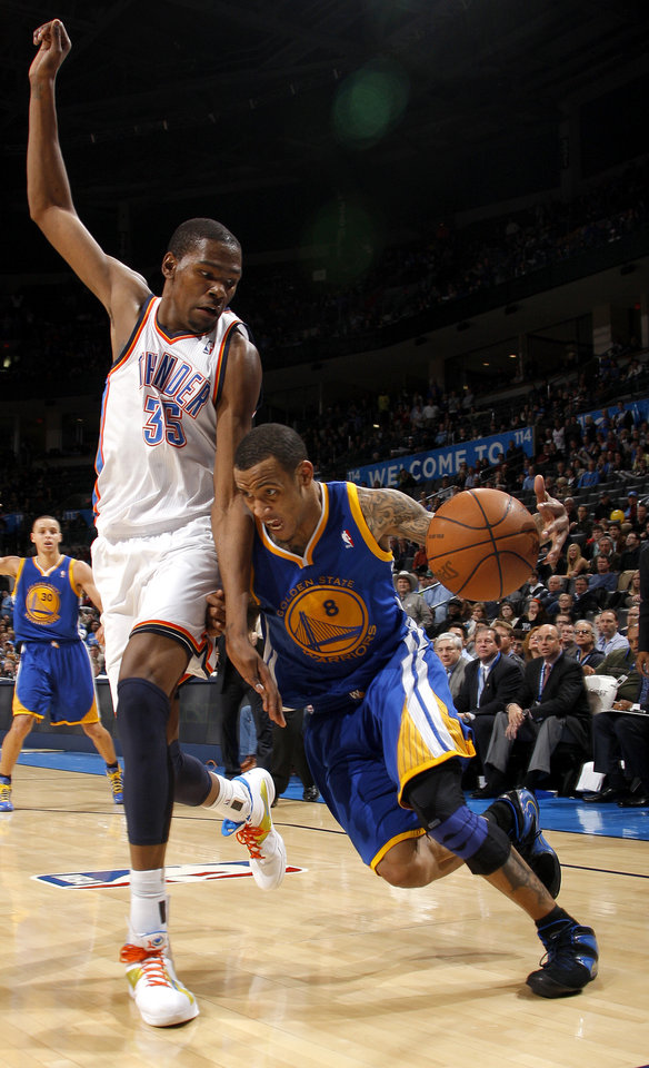Photo - Oklahoma City's Kevin Durant (35) defends Golden State's Monta Ellis (8) during the NBA basketball game between the Oklahoma City Thunder and the Golden State Warriors at the Oklahoma City Arena, Tuesday, March 29, 2011. Photo by Bryan Terry, The Oklahoman