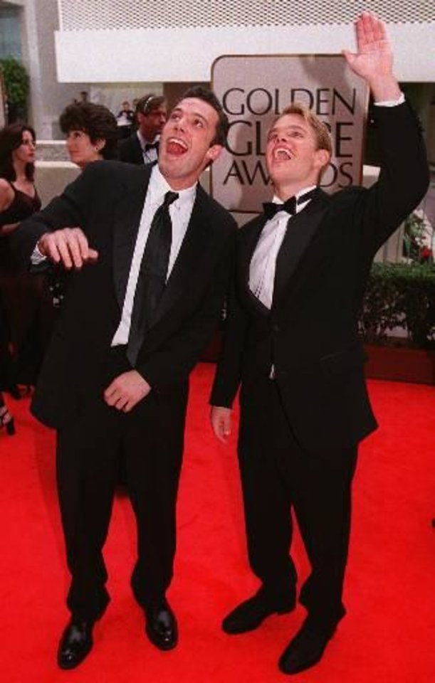 "Actors Matt Damon, right, and Ben Affleck react to fans greeting them from windows at the Beverly Hilton Hotel as they arrive for the 55th Golden Globes in Beverly Hills, Calif., Sunday, Jan. 18, 1998. They won a Golden Globe for Best Screenplay for the film ""Good Will Hunting."" (AP Photo/Chris Pizzello)"