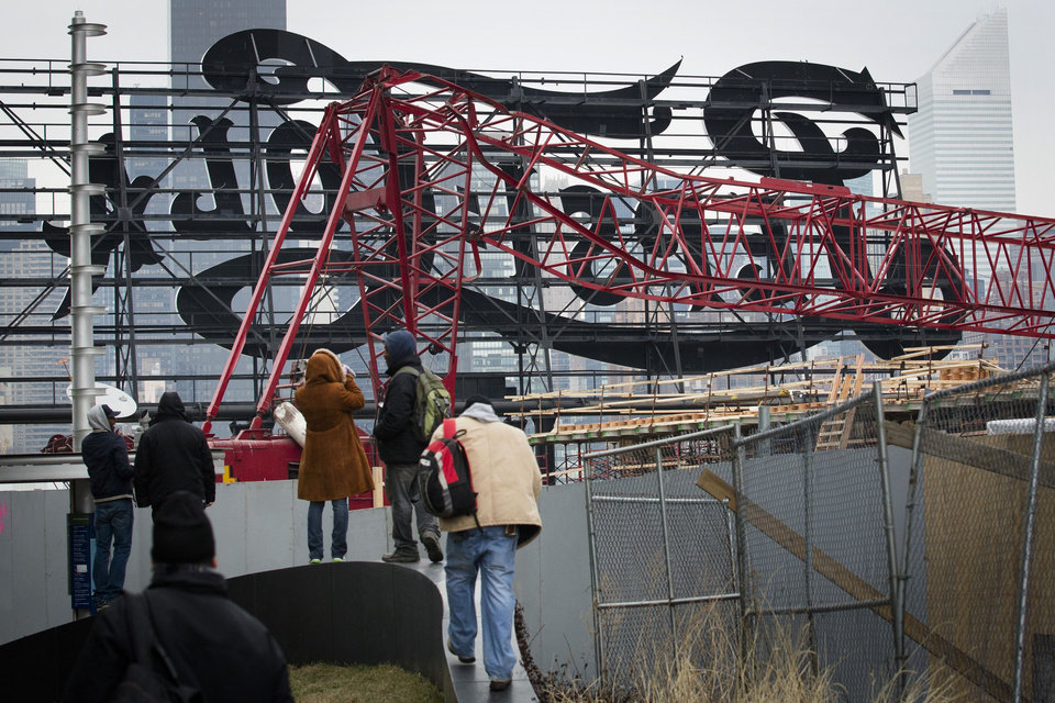 Photo - Onlookers observe a mangled crane at the construction site in the Queens borough of New York where it collapsed, Wednesday, Jan. 9, 2013 behind a big neon