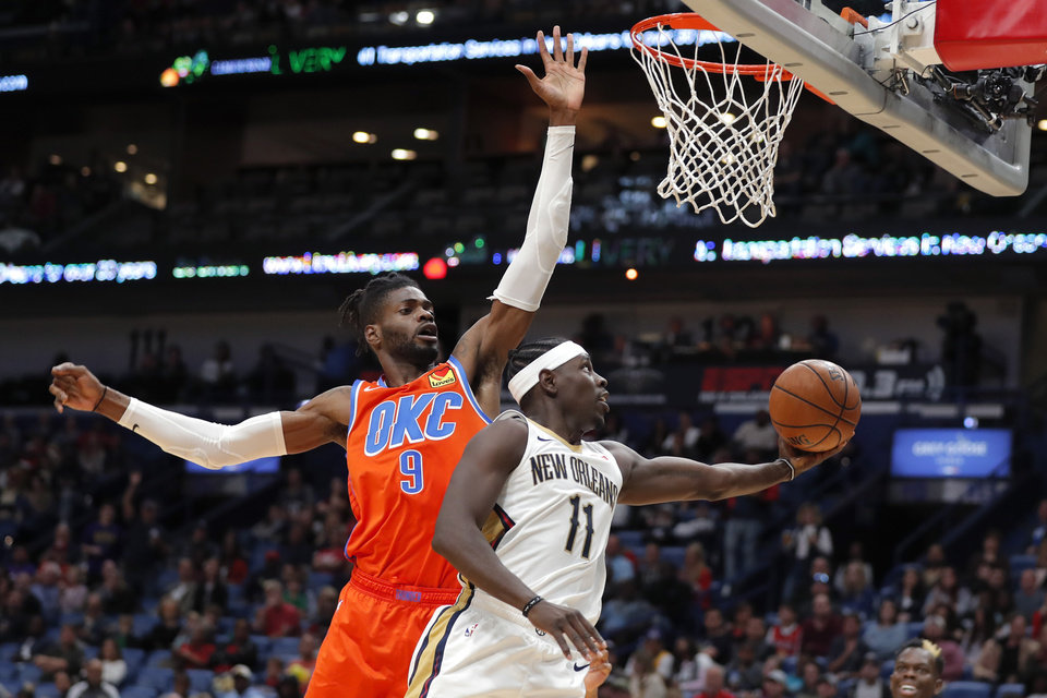 Photo - New Orleans Pelicans guard Jrue Holiday (11) goes to the basket against Oklahoma City Thunder center Nerlens Noel (9) in the second half of an NBA basketball game in New Orleans, Sunday, Dec. 1, 2019.  (AP Photo/Gerald Herbert)
