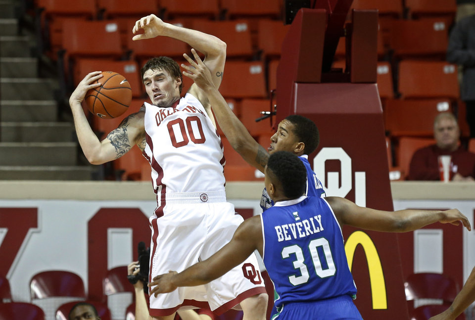 Oklahoma's Ryan Spangler (00) grabs a rebound in front of Texas A&M Corpus Christi forward Jeff Beverly (30) and forward Zane Knowles, rear, during the first half of an NCAA college basketball game in Norman, Okla., Thursday, Dec. 5, 2013. (AP Photo/Sue Ogrocki)