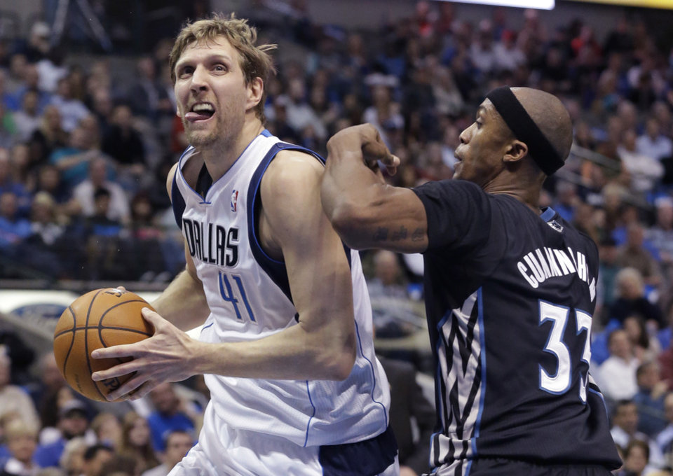 Photo - Dallas Mavericks forward Dirk Nowitzki (41) of Germany drives against Minnesota Timberwolves forward Dante Cunningham (33) during the first half an NBA basketball game Wednesday, March 19, 2014, in Dallas. (AP Photo/LM Otero)