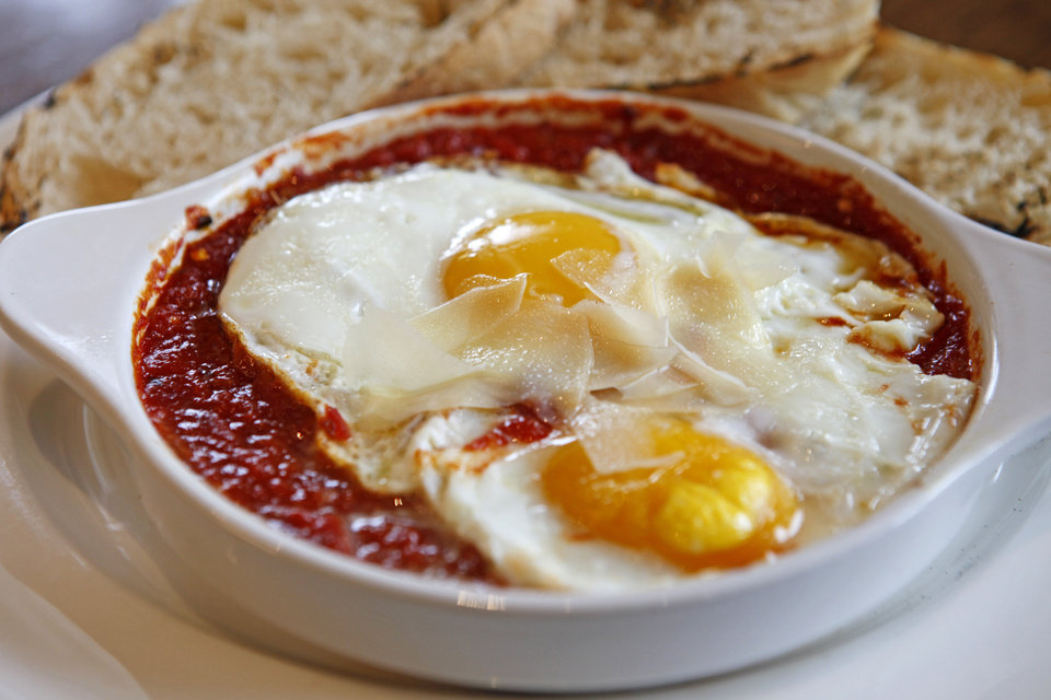 Two sunnyside up eggs over spicy tomato sauce and topped with shaved parmesan cheese makes the brunch item, Spicy Eggs at Stella Modern Italian Restaurant in Oklahoma City. <strong>BRYAN TERRY - THE OKLAHOMAN</strong>