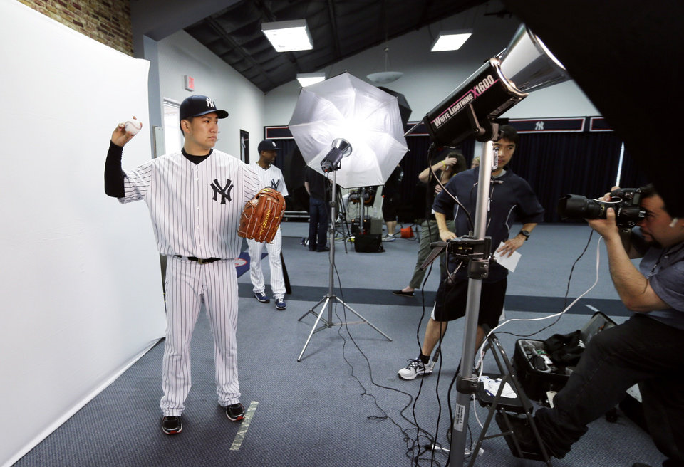 Photo - New York Yankees starting pitcher Masahiro Tanaka poses for a photographer during the Yankees' photo day before a spring training baseball practice Saturday, Feb. 22, 2014, in Tampa, Fla. (AP Photo/Charlie Neibergall)