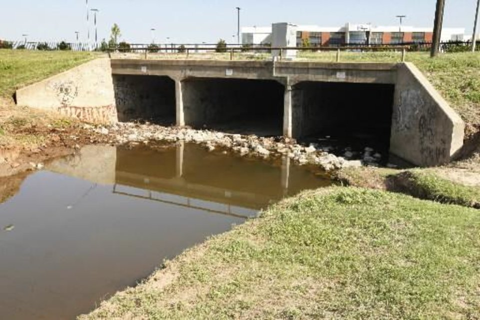 Photo - This is the location where several people were swept away by floodwaters of the May 31'st storms at SW 15th across from the Dell plant in Oklahoma City, OK, Thursday, June 13, 2013. The drainage tunnels pass under the nearly 1/4 mile length of the Dell parking lot before emptying out into the Oklahoma River. Photo by Paul Hellstern, The Oklahoman