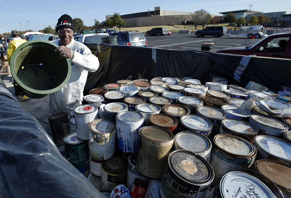 Photo - Michael Holmes loads paint cans on a truck for safe disposal Saturday in Norman.