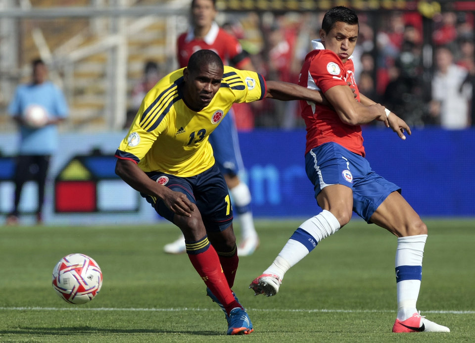 Photo -   Colombia's Edwin Valencia, left, fights for the ball with Chile's Alexis Sanchez during a World Cup 2014 qualifying soccer game in Santiago, Chile, Tuesday, Sept. 11, 2012. Colombia won 3-1. (AP Photo/Luis Hidalgo)