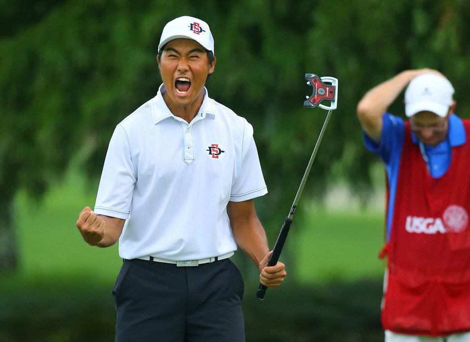 Photo - Gunn Yang, of San Diego, Calif.,  and  his caddy Richard Grice react  to sinking his par putt on the 17th hole during the afternoon round to win the 36-hole championship match of the 2014 U.S. Amateur Championship at Atlanta Athletic Club on Sunday, Aug.17, 2014, in Johns Creek, Ga.  (AP Photo/Atlanta Journal-Constitution, Curtis Compton)  MARIETTA DAILY OUT; GWINNETT DAILY POST OUT; LOCAL TELEVISION OUT; WXIA-TV OUT; WGCL-TV OUT