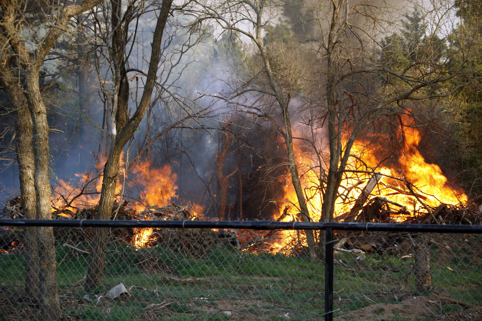 Photo - A fire burns behind homes on E. Wilshire Blvd., Wednesday, April 6, 2011 in Spencer, Okla. Photo by Sarah Phipps, The Oklahoman