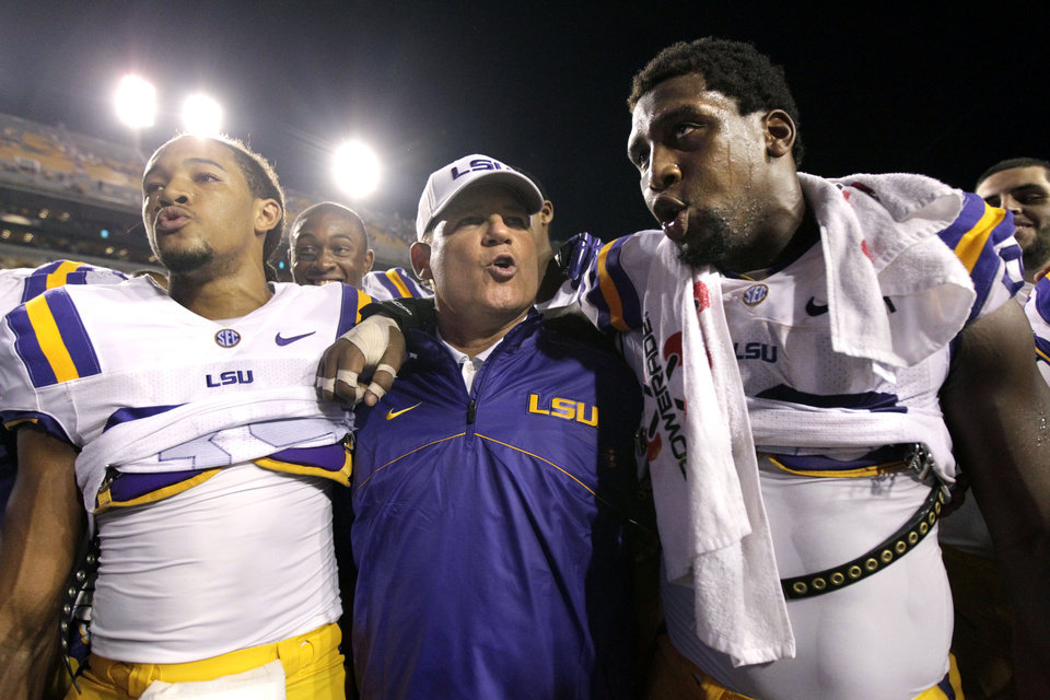 Photo -   In this Sept. 8, 2012 photo, LSU defensive end Sam Montgomery, right, sings the LSU Alma Mater with head coach Les Miles and cornerback Jalen Collins, left, after their NCAA college football game against Washington in Baton Rouge, La. (AP Photo/Gerald Herbert)