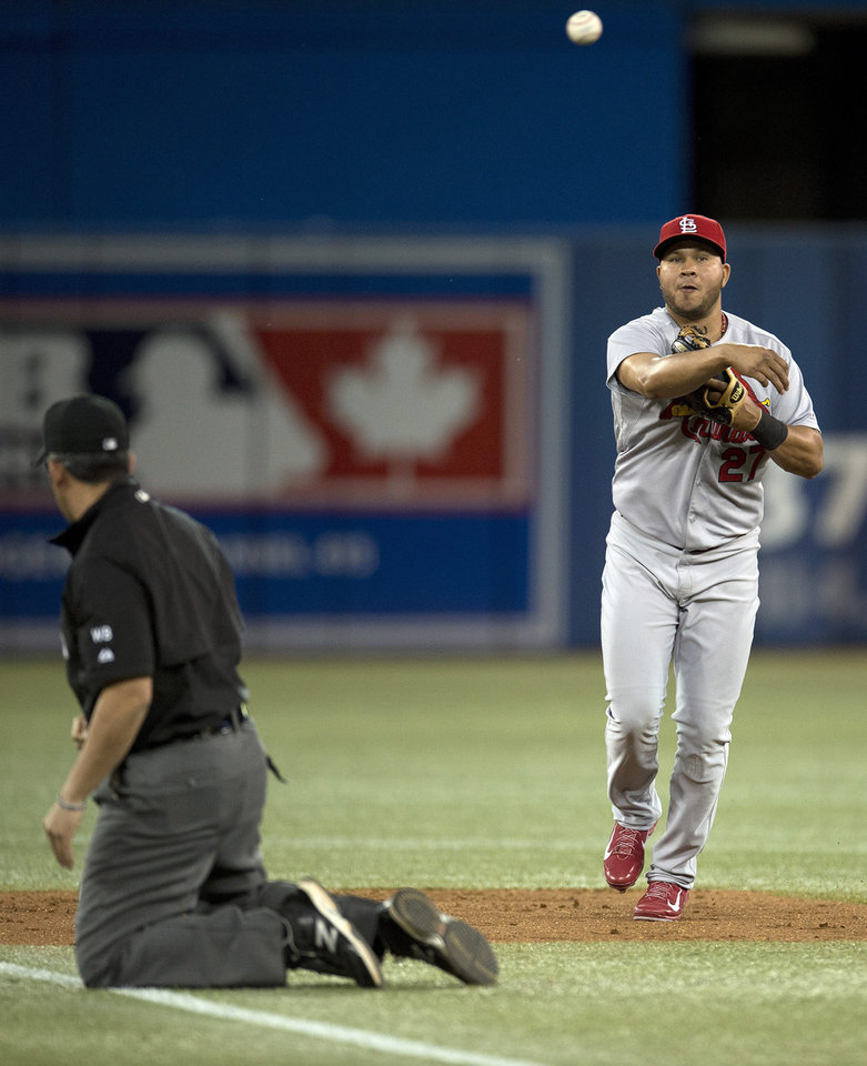 Photo - St. Louis Cardinals short stop Jhonny Peralta (27) turns a triple play on a line drive by Toronto Blue Jays Jose Bautista as second base umpire Manny Gonzalez hits the ground during sixth inning of a baseball game in Toronto on Friday, June 6, 2014. (AP Photo/The Canadian Press, Frank Gunn)