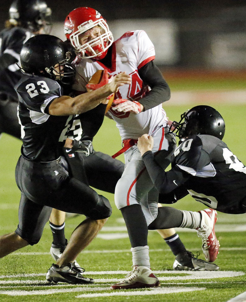 Keaton Argo (84) of Fox is tackled by Devan McKee (20) and Ricky Sanchez (23) of Pond Creek-Hunter during a Class B semifinal high school football playoff game between Pond Creek-Hunter and Fox in Del City, Friday, Nov. 23, 2012. Photo by Nate Billings, The Oklahoman
