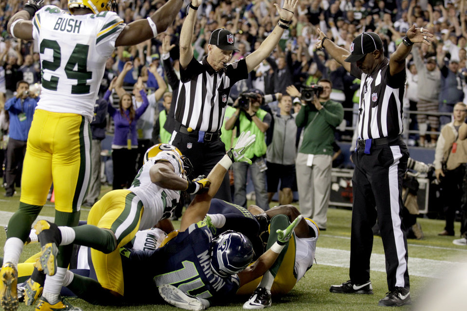 Photo -   FILE - In this Sept. 24, 2012, file photo, an official, rear center, signals for a touchdown by Seattle Seahawks wide receiver Golden Tate, obscured, as another official, at right, signals a touchback on the controversial last play of an NFL football game against the Green Bay Packers in Seattle. The Seahawks won 14-12. The NFL and the referees' union have reached a tentative contract agreement on Wednesday, Sept. 26, ending an impasse that began in June when the league locked out the officials and used replacements instead. (AP Photo/Stephen Brashear, File)
