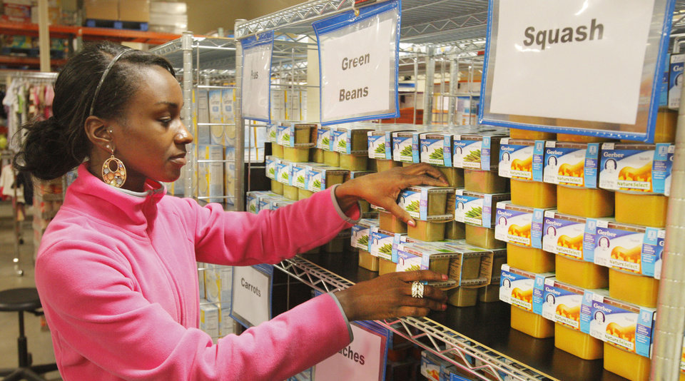 Taniqua Ward, a University of Central Oklahoma junior from Lawton, unpacks baby food and sorts it on the shelves Monday at Infant Crisis Services.