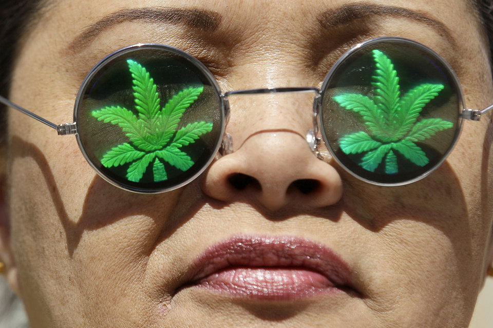Photo -   Medical marijuana supporter Lisa Marie Hopwood poses for photographs while wearing marijuana leaf glasses during a rally outside of the Ronald V. Dellums Federal Building in Oakland, Calif., Friday, April 20, 2012. (AP Photo/Jeff Chiu)