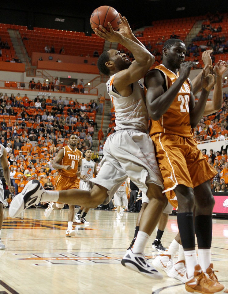 Photo - Oklahoma State's Brian Williams (4) runs into Texas' Alexis Wangmene (20) during an NCAA college basketball game between Oklahoma State University (OSU) and the University of Texas (UT) at Gallagher-Iba Arena in Stillwater, Okla., Saturday, Feb. 18, 2012. Oklahoma State won 90-78. Photo by Bryan Terry, The Oklahoman