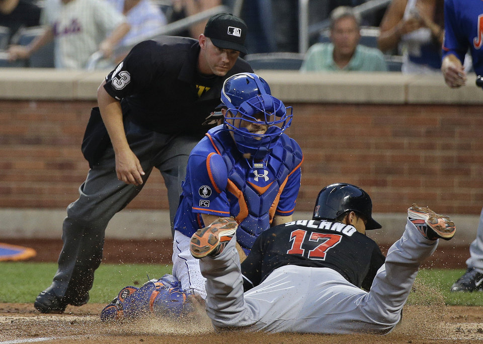 Photo - New York Mets catcher Travis d'Arnaud tags out Miami Marlins second baseman Donovan Solano (17) at the plate after he tried to score from first base on a double by Casey McGehee in the fourth inning of a baseball game, Friday, July 11, 2014, in New York. (AP Photo/Julie Jacobson)