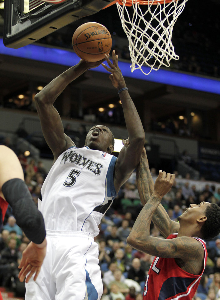Photo - Minnesota Timberwolves center Gorgui Dieng (5) puts up a shot over Atlanta Hawks guard Louis Williams (3) during the second half of an NBA basketball game, Wednesday, March 26, 2014, in Minneapolis. Dieng had 15 points and 15 rebounds on the night as Minnesota won 107-83. (AP Photo/Paul Battaglia)