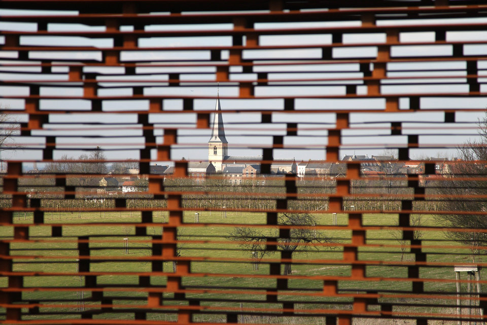 Photo - In this Feb. 20, 2013 file photo, a church is pictured through the steel layers of a see-through church on a hilltop in Borgloon, 80 km (50 miles) East of Brussels. The artistic vision of the church is made of rusty steel beams separated by gaps, and its austere beauty won it an international architecture prize. Yet the eerie desolation of the see-through installation has also turned into a reflection on the state of Roman Catholicism on a religion-weary continent where real churches, like the dozen dotting the hills of this verdant area, increasingly lose their flock and function. (AP Photo/Yves Logghe, file)