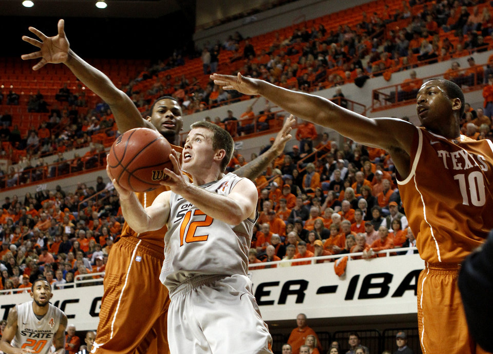 Photo - Oklahoma State's Keiton Page (12) goes between Texas' Jaylen Bond (2) and Jonathan Holmes (10) during an NCAA college basketball game between Oklahoma State University (OSU) and the University of Texas (UT) at Gallagher-Iba Arena in Stillwater, Okla., Saturday, Feb. 18, 2012. Oklahoma State won 90-78. Photo by Bryan Terry, The Oklahoman