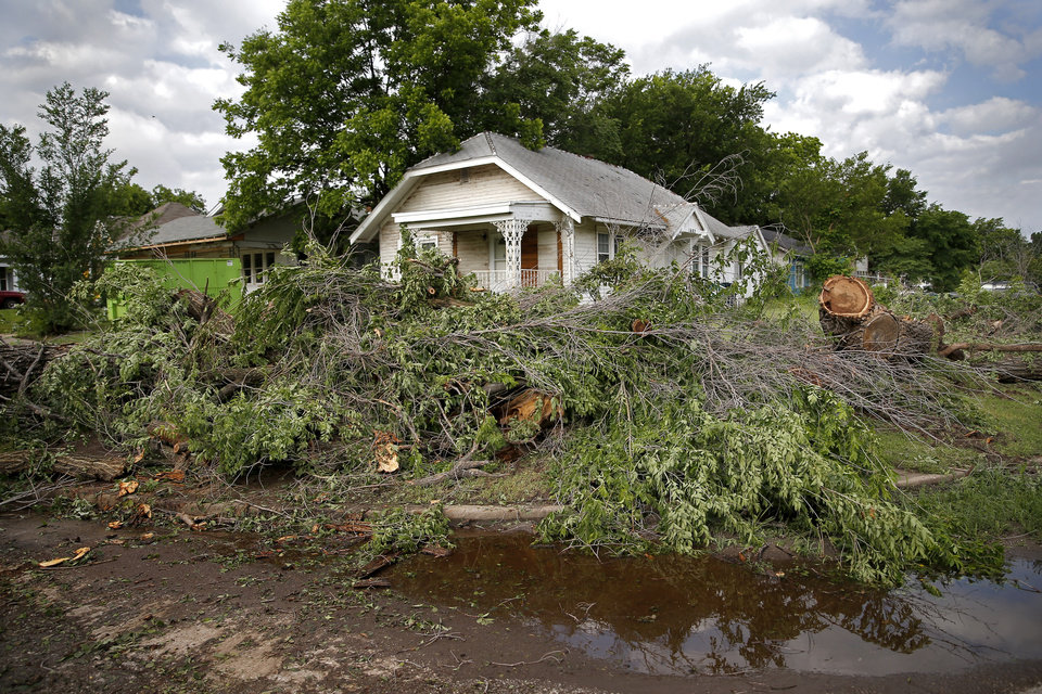 Photo - A house near 21st and McKinley is surrounded by trees after an apparent tornado moved through the area in Oklahoma City, Sunday, May 26, 2019. Luna said the sirens sounded and it instantly became windy. He stood next to an interior wall with his 12 year old daughter.  [Sarah Phipps/The Oklahoman]