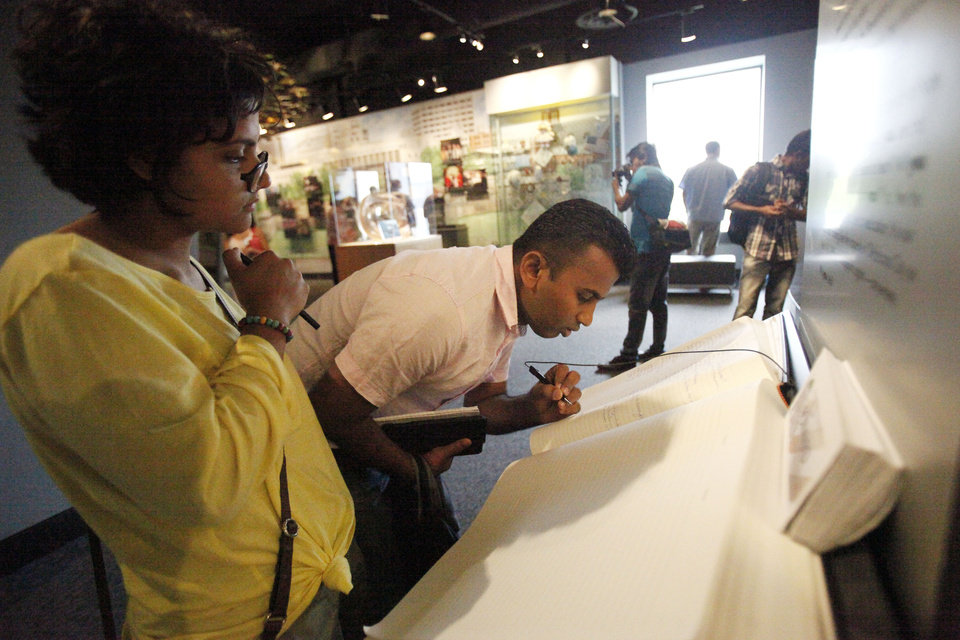 Photo -  Rifti Ali (24) of Sri Lanka, (right) stops to sign the guestbook at the OKC Bombing Museum on Friday, May 31, 2013. Photo by Aliki Dyer The Oklahoman