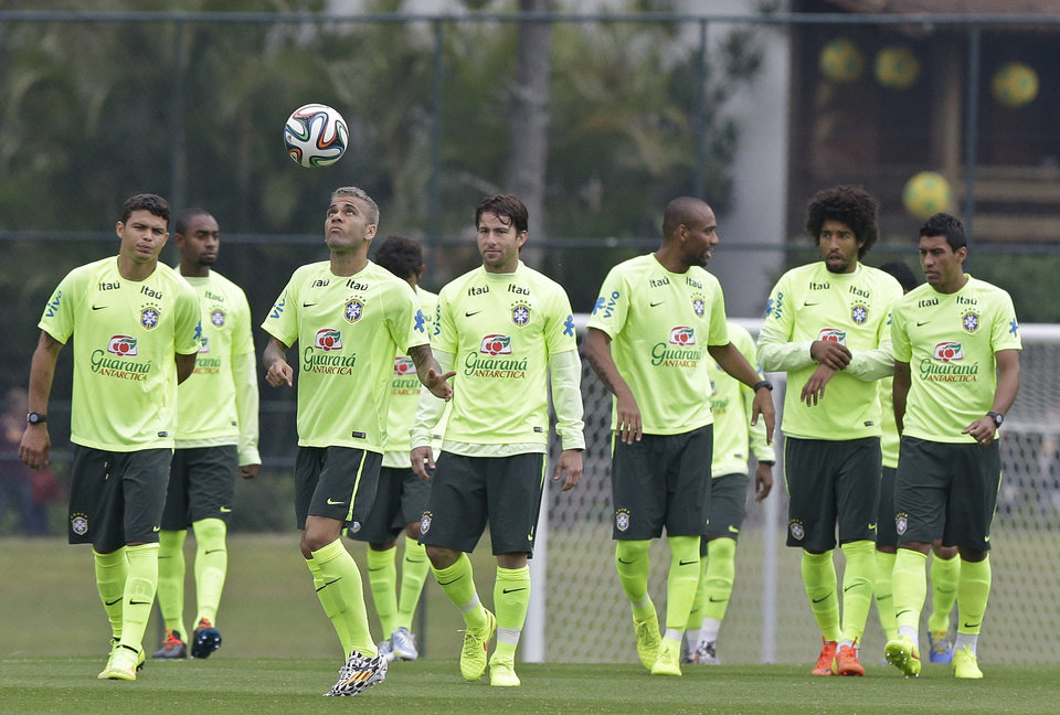 Photo - Brazil's Dani Alves, third from left, plays with the ball as he practices with teammates during a training session of the Brazilian national soccer team at the Granja Comary training center in Teresopolis, Brazil, Saturday, June 21, 2014. Brazil plays in group A of the 2014 soccer World Cup. (AP Photo/Andre Penner)