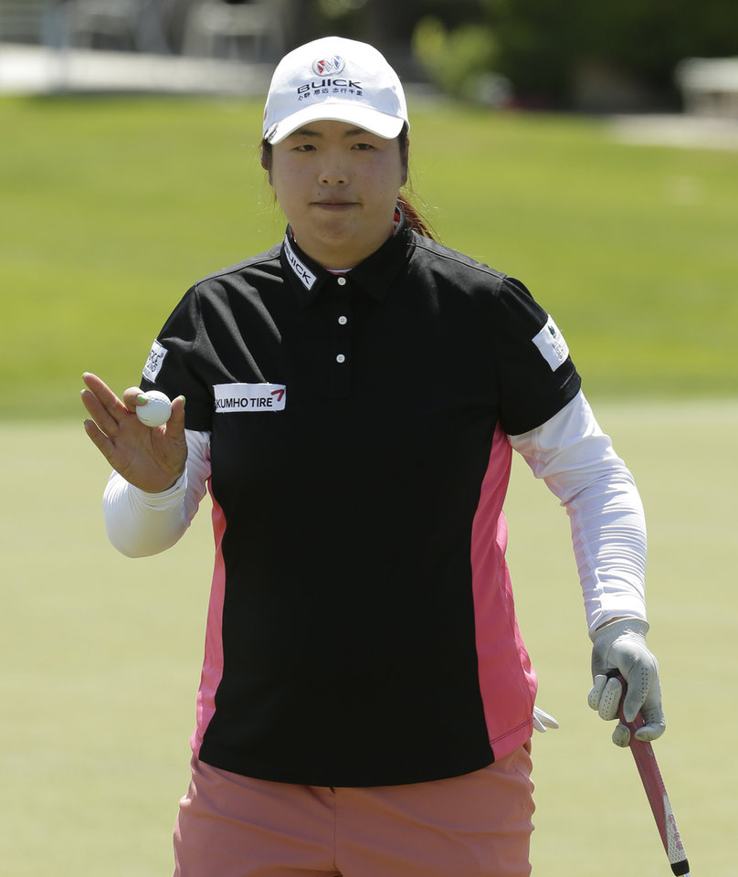 Photo - Shanshan Feng, of China, waves after rolling in a birdie putt on the 16th hole during the first round at the Kraft Nabisco Championship golf tournament on Thursday, April 3, 2014, in Rancho Mirage, Calif. (AP Photo/Chris Carlson)