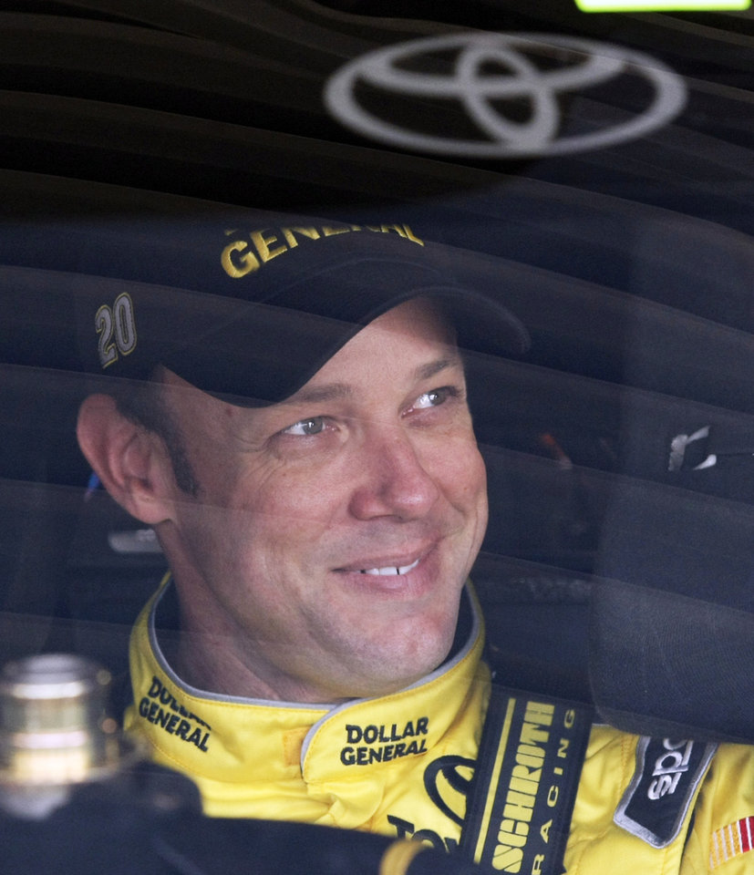 Photo - Driver Matt Kenseth sits in his car before practice for Sunday's NASCAR Sprint Cup series auto race at Kansas Speedway Friday, Oct. 4, 2013, in Kansas City, Kan. (AP Photo/Colin E. Braley)