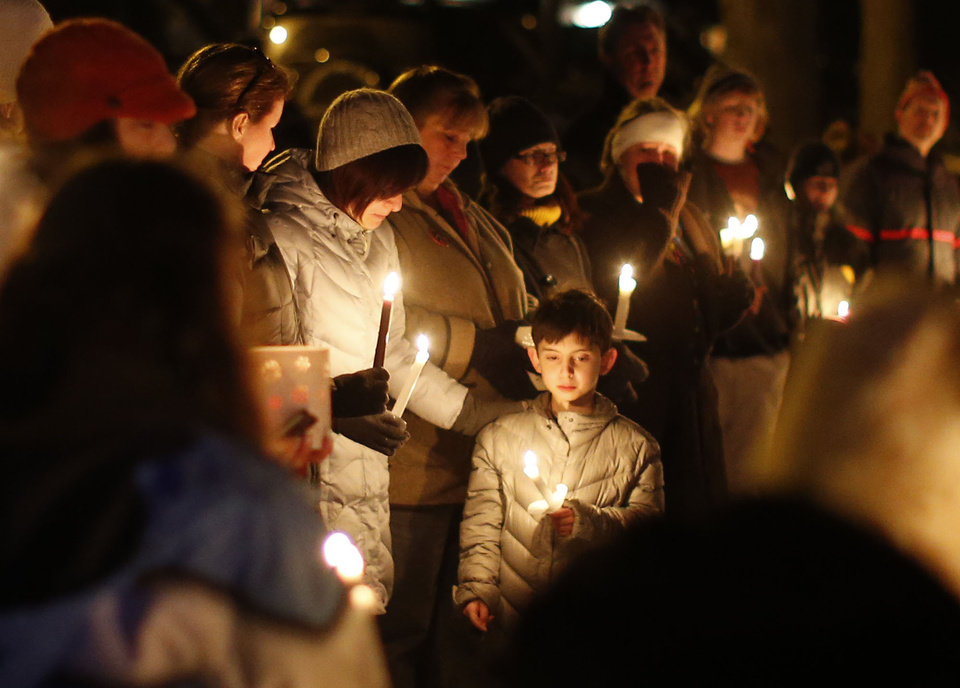 Photo - Mourners gather for a candlelight vigil at Ram's Pasture to remember shooting victims, Saturday, Dec. 15, 2012 in Newtown, Conn.  A gunman walked into Sandy Hook Elementary School in Newtown Friday and opened fire, killing 26 people, including 20 children. (AP Photo/Jason DeCrow) ORG XMIT: CTJD126